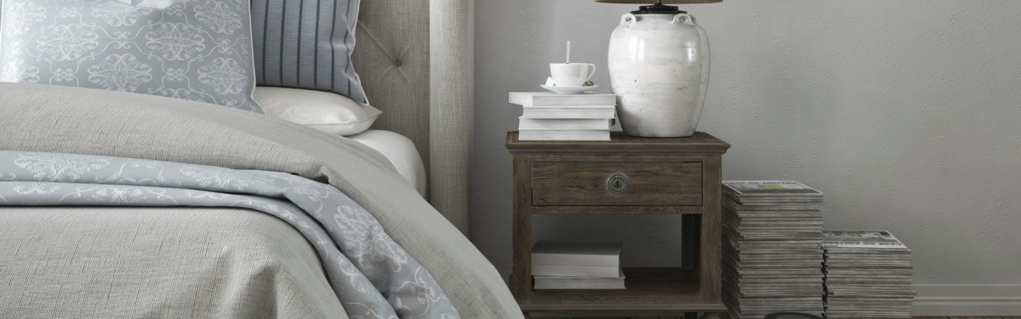 Photography of a bedroom and nightstand with a lamp, a stack of books, and a cup of coffee