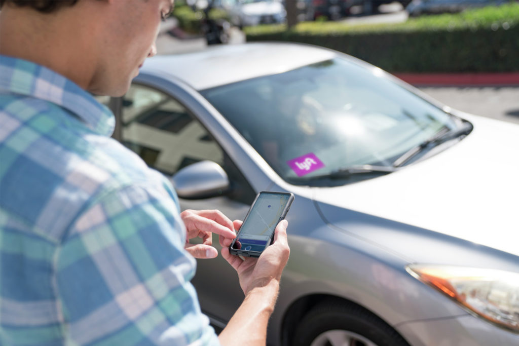 Photography of a young man setting up a ride with Lyft